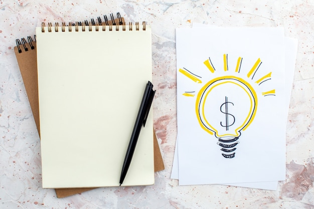 Vue de dessus idée d'entreprise ampoule dessin sur papier stylo sur bloc-notes sur table