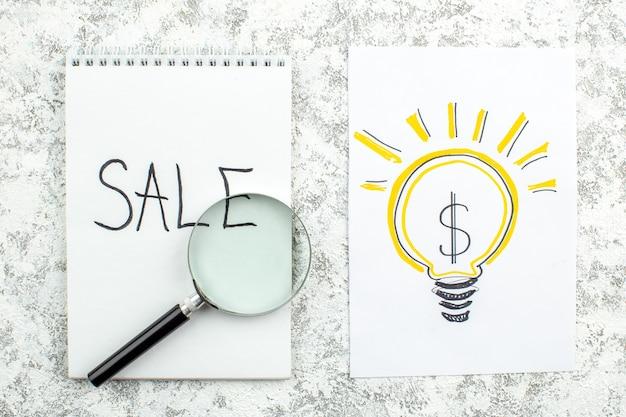 Vue de dessus idée d'entreprise ampoule dessin sur papier vente écrit sur ordinateur portable lupa sur table