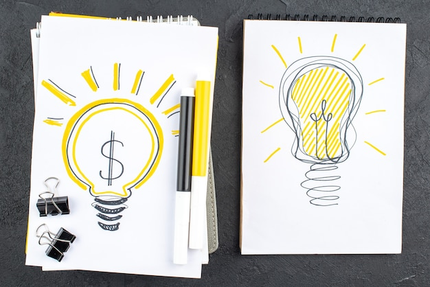 Vue de dessus des idées d'ampoules sur des cahiers marqueurs jaunes et noirs pinces à reliure noires sur une surface noire