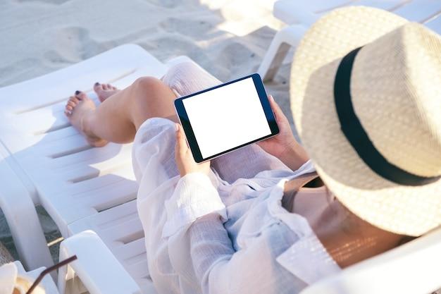 Vue de dessus image de maquette d'une femme tenant un tablet pc noir avec écran de bureau vide tout en fixant sur une chaise de plage sur la plage