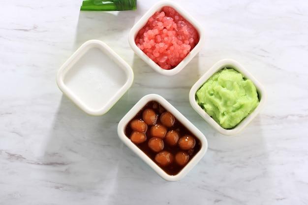 Vue de dessus ingrédient d'es bubur sumsum ou es bubur lemu bandung, bouillie traditionnelle populaire de java occidental, à base de farine de riz, de candil (boule de riz gluant) et de perle de tapioca. copier l'espace pour le texte