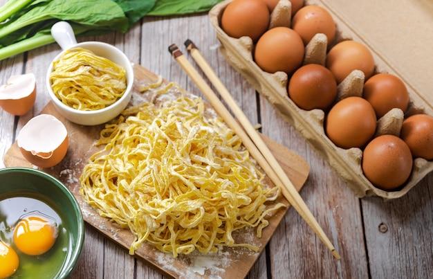 Vue de dessus des ingrédients des nouilles aux œufs comme les œufs, la farine en poudre, le jaune d'oeuf, la planche à découper et les baguettes