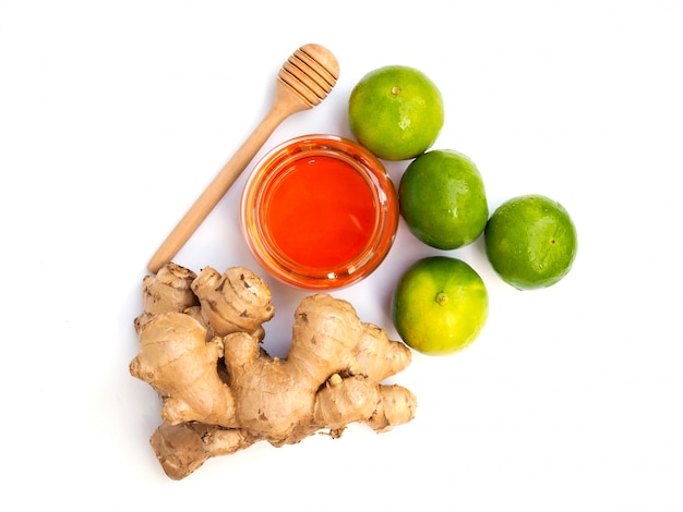 Vue de dessus des ingrédients pour les boissons à base de jus ou le thé avec du miel, du citron vert et du gingembre isolé sur un espace blanc.