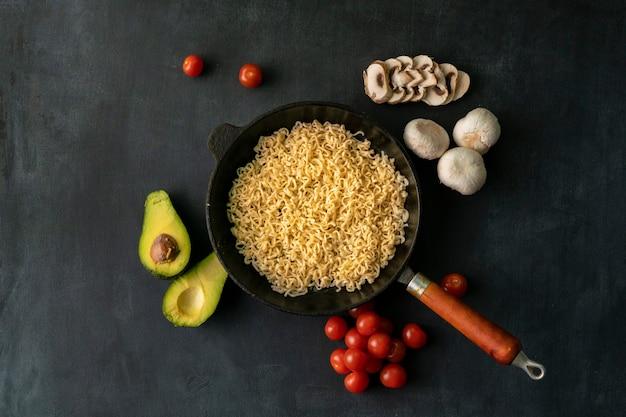 Vue de dessus des ingrédients pour la cuisson des pâtes sur la table, avocat, nouilles à la poêle, champignons