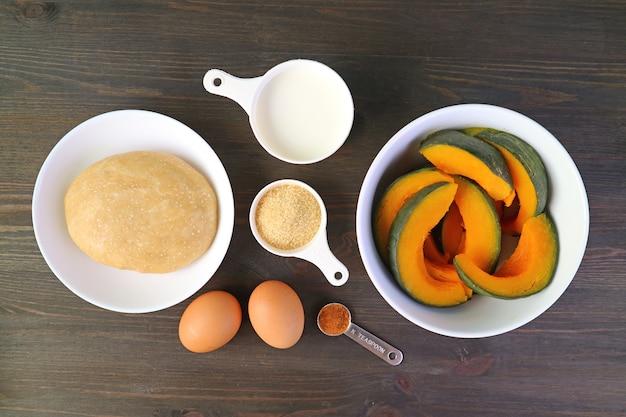 Vue de dessus des ingrédients pour la cuisson de la tarte à la citrouille fraîche sur le fond en bois noir