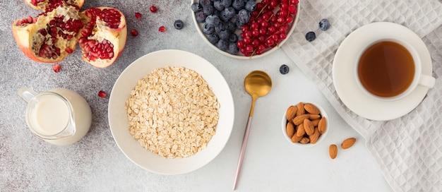Vue de dessus des ingrédients pour un petit-déjeuner sain - flocons d'avoine, noix, bleuets, fruits, lait ou yaourt. mise à plat des aliments naturels de saison bio. mise à plat, fond clair