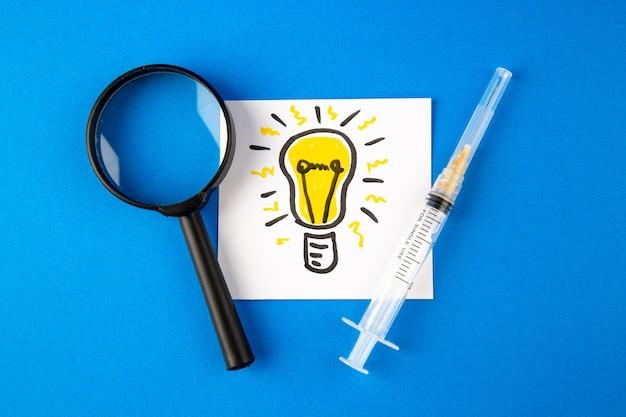 Vue de dessus injection antivirus avec loupe et ampoule dessin sur surface bleue virus de la santé de l'hôpital covid- laboratoire pandémique science des médicaments