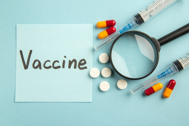 Vue de dessus des injections d'antivirus avec des pilules et avec covid dessin sur une surface bleue laboratoire science pandémie covid- virus hôpital couleur santé du vaccin
