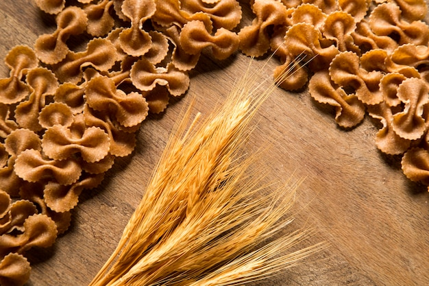 Vue de dessus de l'intégrale de pâtes non cuites sur une surface en bois