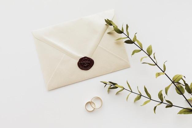 Vue de dessus invitation de mariage scellée avec bagues de fiançailles