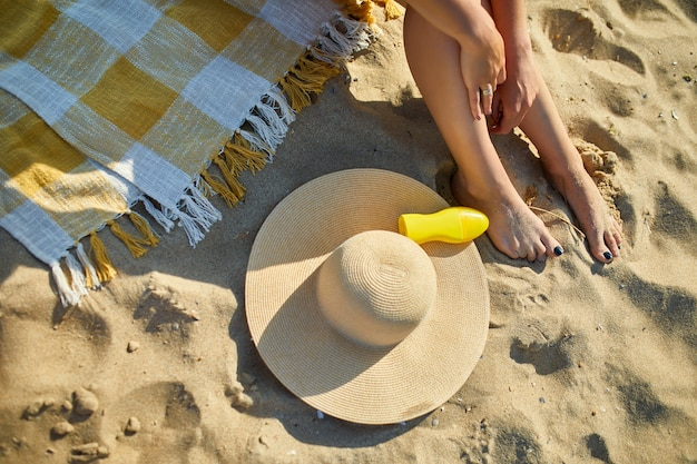 Vue de dessus jambe de femme assise sur la plage de sable