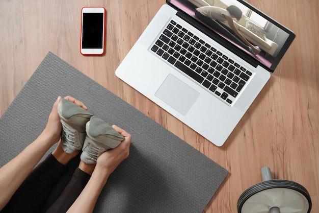 Vue de dessus des jambes d'étirement des femmes à la maison à l'aide d'un ordinateur portable pour les cours en ligne