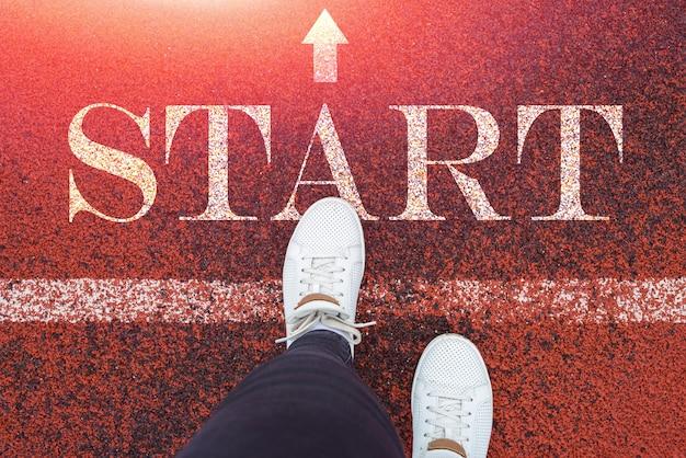 La vue de dessus des jambes féminines en baskets blanches fait un pas au début. le mot commence sur un tapis roulant. notion de nouvel an.
