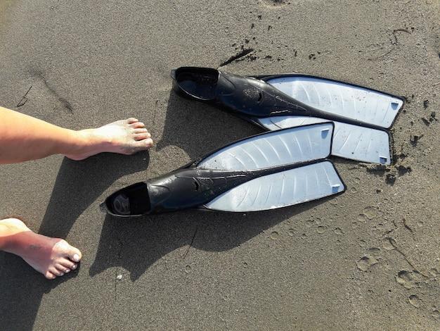 Vue de dessus des jambes de femme et des épingles de plongée sur la côte sablonneuse