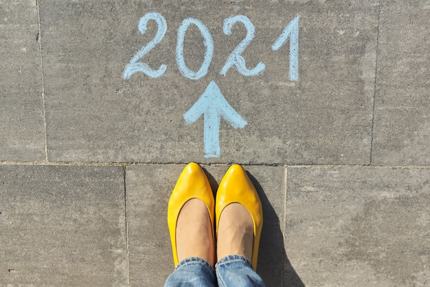 Vue de dessus sur les jambes de la femme et texte 2021 écrit à la craie sur le trottoir gris