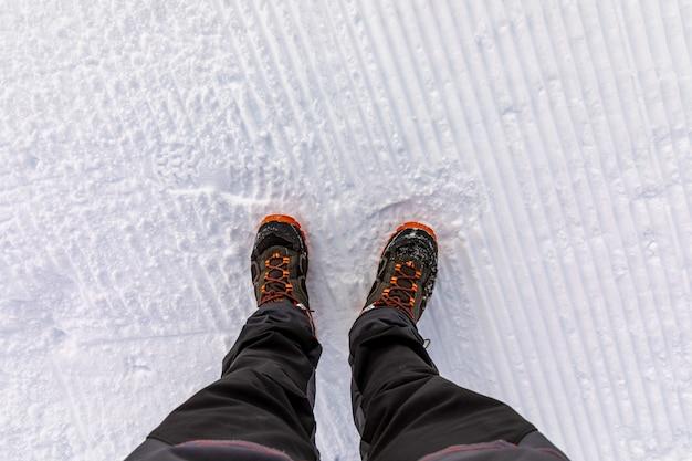 Vue de dessus des jambes sur la neige