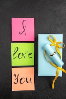 Vue de dessus je t'aime écrit sur un anneau de notes autocollantes colorées sur un cadeau sur fond darkc