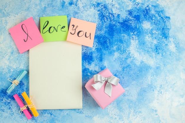 Vue de dessus je t'aime écrit sur des notes autocollantes colorées faites défiler les papiers de souhaits bloc-notes cadeau sur l'espace libre de la table