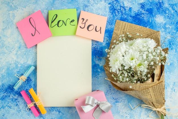 Vue de dessus je t'aime écrit sur des notes autocollantes colorées faites défiler les papiers de souhaits fleurs blanches cahier sur table