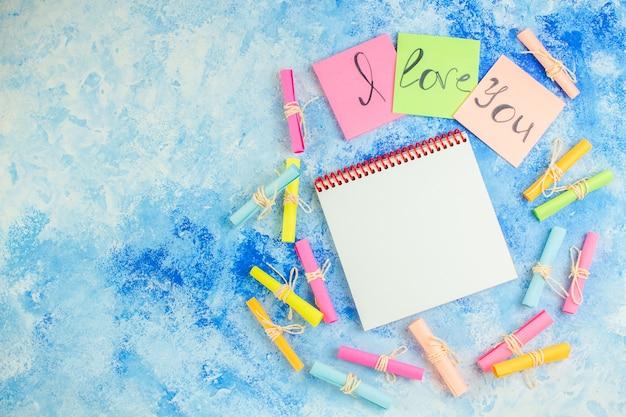 Vue de dessus je t'aime écrit sur des notes autocollantes faites défiler les papiers de souhaits bloc-notes sur fond bleu copie place