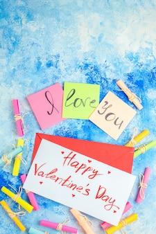 Vue de dessus je t'aime écrit sur des notes autocollantes faites défiler les papiers de souhaits joyeuse saint valentin écrit sur papier sur fond bleu