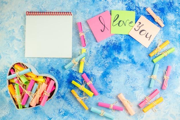 Vue de dessus je t'aime écrit sur des notes autocollantes pour faire défiler les papiers de souhaits dans une boîte en forme de coeur sur fond bleu