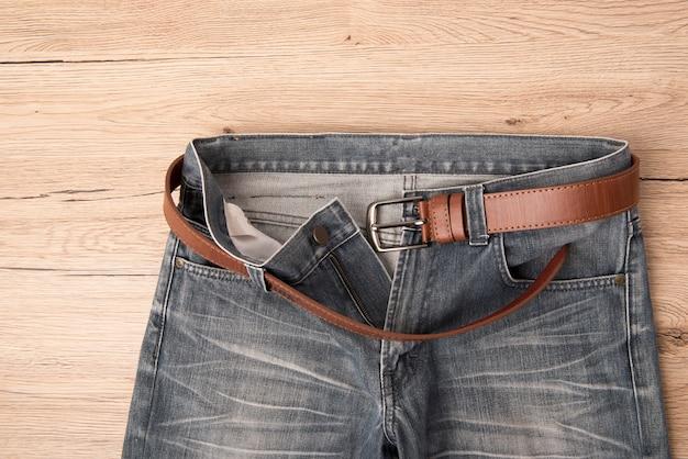 Vue de dessus jeans et ceinture de cuir rythme sur fond de bois.