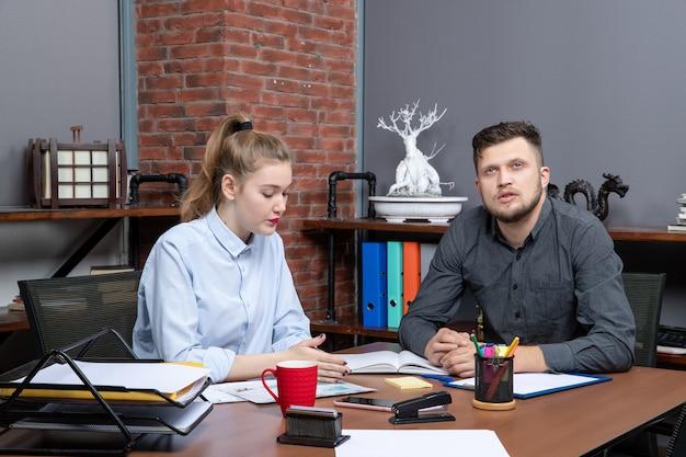 Vue de dessus d'une jeune assistante de bureau et de son collègue masculin assis à la table pour discuter d'un problème important au bureau