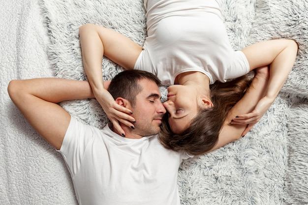 Vue de dessus jeune couple au repos au lit