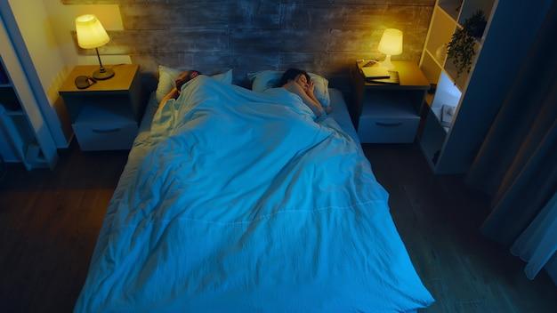 Vue de dessus d'un jeune couple dormant dans une pièce au clair de lune bleu venant par la fenêtre.