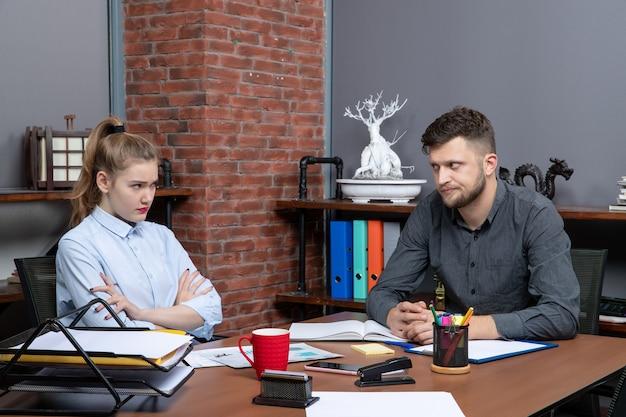Vue de dessus d'une jeune équipe de bureau insatisfaite assise à la table pour discuter d'un problème important au bureau