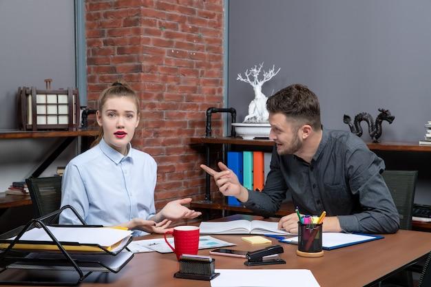 Vue de dessus d'une jeune équipe de bureau occupée assise à la table pour discuter d'un problème important au bureau