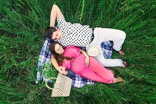 Vue de dessus de la jeune famille. homme et femme se trouvent sur une couverture parmi les hautes herbes. sac avec un bouquet de fleurs et canotier.