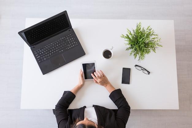Vue de dessus d'une jeune femme d'affaires travaillant au bureau avec la tablette.