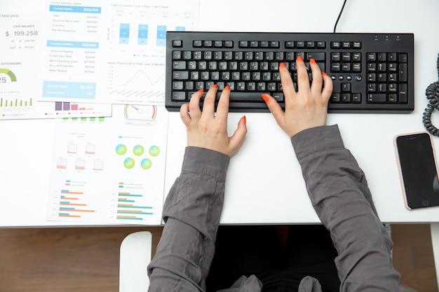 Une vue de dessus jeune femme d'affaires travaillant sur son ordinateur portable sur la table avec le téléphone et la technologie des activités professionnelles graphiques