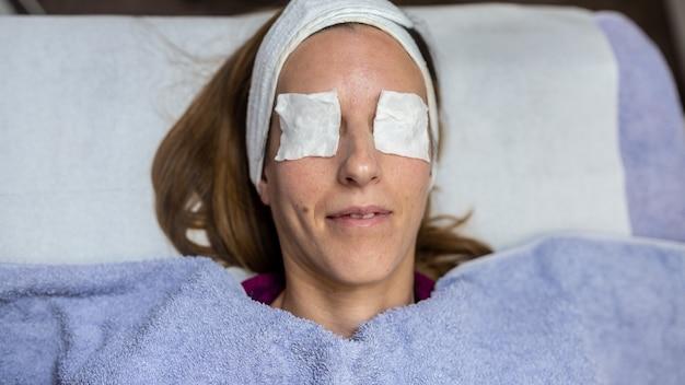 Vue de dessus d'une jeune femme allongée sur un bureau de massage avec des tampons hydratants en coton sur les yeux se relaxant pendant qu'elle se fait dorloter.