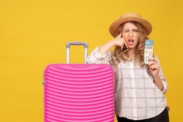 Vue de dessus d'une jeune femme ambitieuse confiante portant un chapeau montrant un billet et debout près de son sac rose