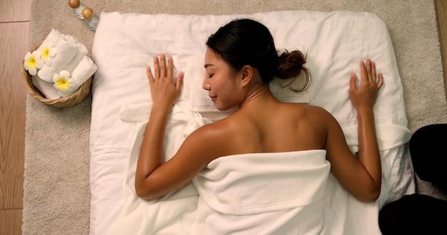 Vue de dessus de la jeune femme asiatique dormant au salon spa
