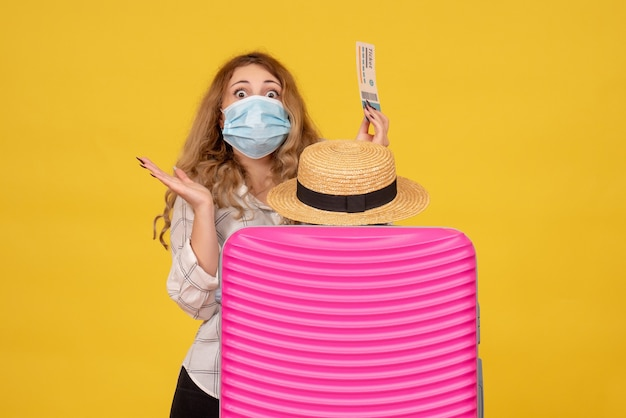 Vue de dessus d'une jeune femme choquée portant un masque montrant un billet et debout derrière son sac rose
