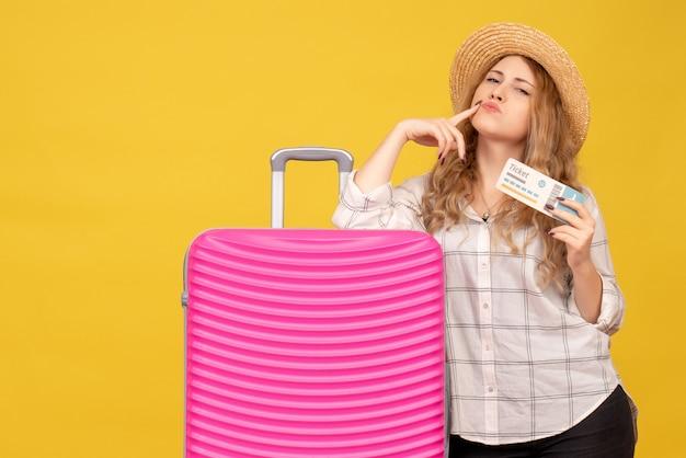 Vue de dessus de la jeune femme confiante portant un chapeau tenant un billet et debout près de son sac rose
