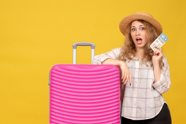 Vue de dessus de la jeune femme confuse portant un chapeau tenant un billet et debout près de son sac rose