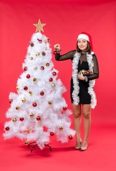 Vue de dessus de la jeune femme dans une robe noire avec chapeau de père noël et décoration de l'arbre du nouvel an sur le rouge