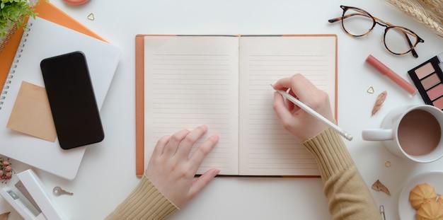 Vue de dessus de la jeune femme écrit sur un cahier vierge dans le concept d'espace de travail féminin beige chaud avec maquillage