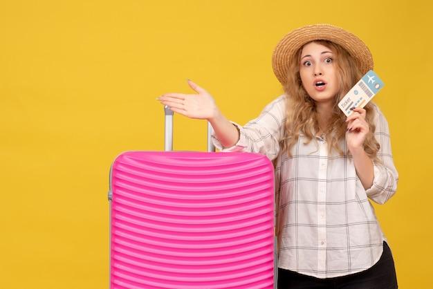 Vue de dessus de la jeune femme émotionnelle curieuse portant un chapeau tenant un billet et debout près de son sac rose