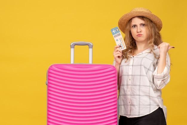 Vue de dessus de la jeune femme émotionnelle portant un chapeau montrant un billet et debout près de son sac rose pointant vers l'arrière