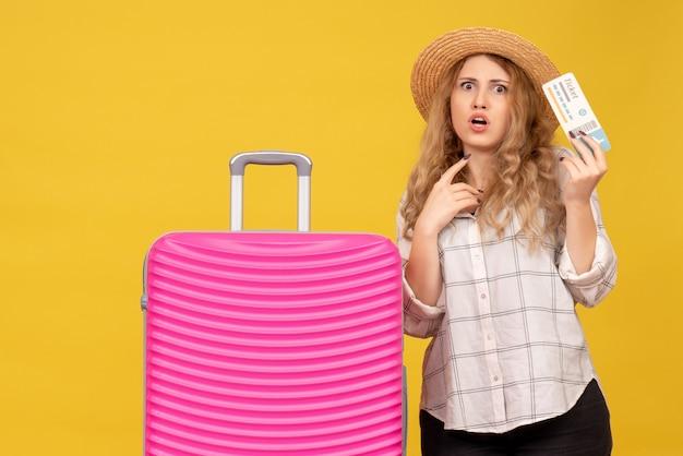 Vue de dessus d'une jeune femme inquiète portant un chapeau tenant un billet et debout près de son sac rose