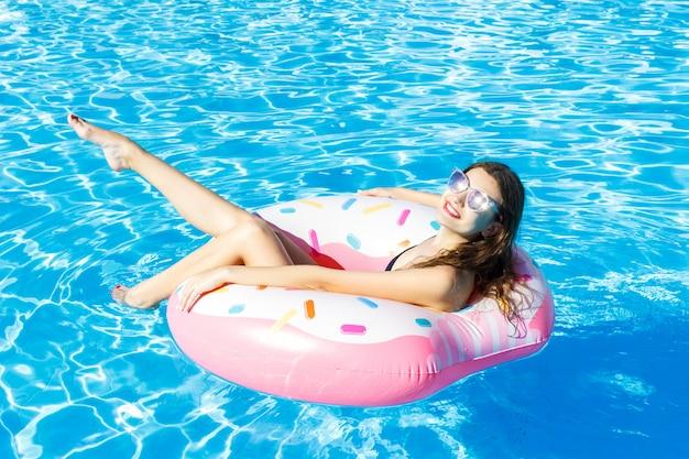 Vue de dessus de la jeune femme nage avec cercle rose dans la piscine