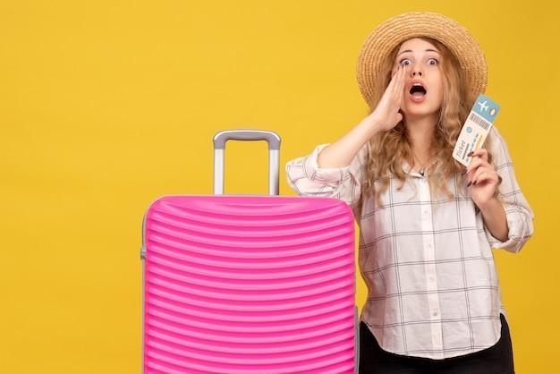Vue de dessus de la jeune femme portant un chapeau tenant un billet et debout près de son sac rose appeler quelqu'un