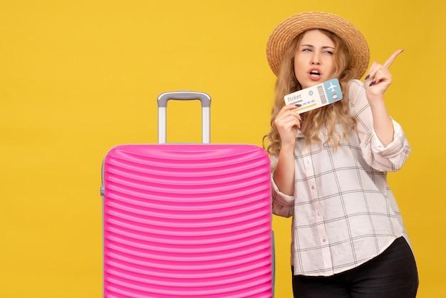 Vue de dessus de la jeune femme portant un chapeau tenant un billet et debout près de son sac rose pointant quelque chose sur le côté gauche