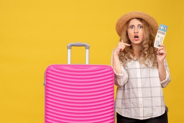 Vue de dessus de la jeune femme portant un chapeau tenant un billet et debout près de son sac rose se pointant